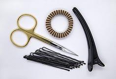 Diversos artículos para el cuidado del pelo y del clavo de las mujeres en el fondo blanco, pinzas de pelo, banda elástica, tijera foto de archivo