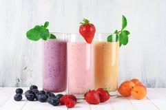 Diversos batidos de leche con las frutas imagen de archivo