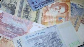 Diversos billetes de banco asiáticos que giran en placa giratoria Moneda internacional de Asia Dinero tradicional del efectivo almacen de video