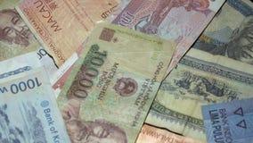 Diversos billetes de banco asiáticos que giran en placa giratoria Moneda internacional de Asia Dinero tradicional del efectivo almacen de metraje de vídeo