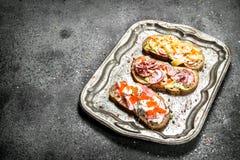 Diversos bocadillos con el caviar rojo, el tocino, el queso y verduras frescas en una bandeja de acero Imagenes de archivo