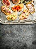 Diversos bocadillos con el caviar rojo, el tocino, el queso y verduras frescas en una bandeja de acero Fotos de archivo