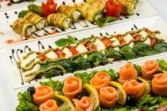 Diversos bocados para comer el día de fiesta en las placas blancas en el fondo blanco Cocina, menú, concepto de la comida Plato d Imagenes de archivo