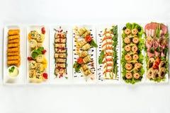 Diversos bocados para comer el día de fiesta en las placas blancas en el fondo blanco Cocina, menú, concepto de la comida Plato d Foto de archivo libre de regalías