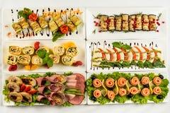 Diversos bocados para comer el día de fiesta en las placas blancas en el fondo blanco Cocina, menú, concepto de la comida Plato d Fotos de archivo libres de regalías