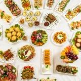 Diversos bocados para comer el día de fiesta en las placas blancas en el fondo blanco Cocina, menú, concepto de la comida Plato d Foto de archivo