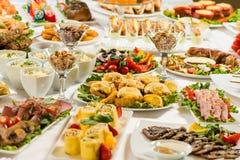 Diversos bocados para comer el día de fiesta en las placas blancas en el fondo blanco Cocina, menú, concepto de la comida Plato d Imagen de archivo libre de regalías