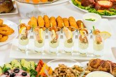 Diversos bocados para comer el día de fiesta en las placas blancas en el fondo blanco Cocina, menú, concepto de la comida Plato d Fotos de archivo
