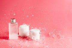 Diversos botellas, tarros y envases con los cosméticos en rosa con salpicar las aguas Imagenes de archivo