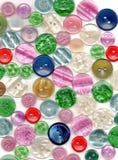 Diversos botones en el fondo blanco, visión superior Foto de archivo libre de regalías