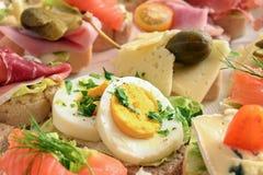 Diversos canapes con el huevo, el queso, el jamón y los salmones en el buffet frío, opinión del primer foto de archivo libre de regalías