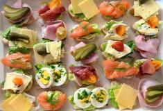 Diversos canapes con el huevo, el queso, el jamón y los salmones en una bandeja en el buffet frío, opinión de alto ángulo desde a imágenes de archivo libres de regalías