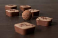 Diversos caramelos de chocolate en una tabla de madera Fotografía de archivo