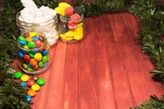 Diversos caramelos del color en fondo de madera con malla Copie el espacio Fotografía de archivo
