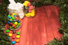 Diversos caramelos del color en fondo de madera con malla Copie el espacio Imagen de archivo libre de regalías