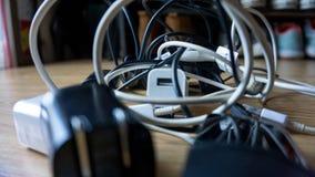 Diversos cargadores USB blancos y negros de los cables y atan con alambre enredado y en caos fotografía de archivo libre de regalías