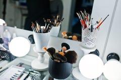 Diversos cepillos del maquillaje en la tabla de mirro beaty del fondo del estudio Fotos de archivo