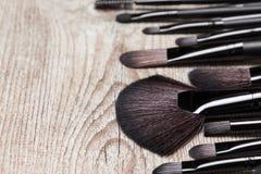 Diversos cepillos del maquillaje en superficie de madera lamentable Imágenes de archivo libres de regalías