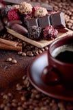 Diversos chocolates y taza de café sólo imagen de archivo