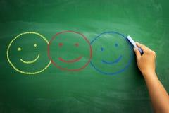Diversos colores de los smiley exhaustos en la pizarra Imagen de archivo libre de regalías