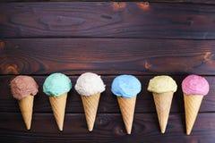 Diversos conos de helado en la tabla de madera, endecha plana Fotos de archivo libres de regalías