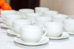 Diversos copos de café branco no banquete Imagem de Stock Royalty Free