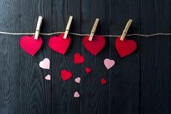 Diversos corazones con las pinzas en fondo Fotos de archivo
