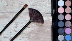 Diversos cosméticos del maquillaje en la tabla de madera blanca rústica Foto de archivo libre de regalías