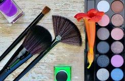 Diversos cosméticos del maquillaje en la tabla de madera blanca rústica Fotografía de archivo
