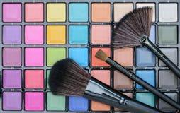 Diversos cosméticos del maquillaje en la tabla de madera blanca rústica Foto de archivo