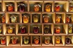 Diversos cotos conservados de la verdura en tarros en el estante de madera Imagen de archivo libre de regalías