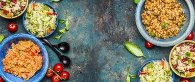 Diversos cuencos de ensalada sanos en fondo oscuro del vintage Ensaladas del país en cuencos rústicos Bufete de ensaladas, visión Imagen de archivo