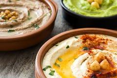 Diversos cuencos del hummus Hummus del garbanzo, hummus del aguacate y hummus de las lentejas Imágenes de archivo libres de regalías