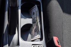 Diversos dólares americanos das cédulas encontram-se na ameia do console central do carro O dinheiro no carro Imagens de Stock Royalty Free