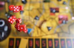 Diversos dados vermelhos de rolamento caem em uma tabela com boardgame Momentos de Gameplay Fotos de Stock Royalty Free