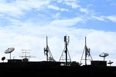 Diversos dispositivos de comunicación de la silueta en tejado Fotos de archivo
