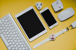 Diversos dispositivos de la oficina en el fondo amarillo, visión superior Fotos de archivo libres de regalías