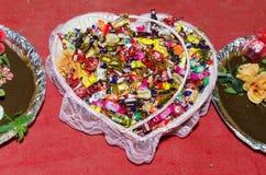 Diversos dulces en la cesta de la boda en un fondo rojo Compromiso del día de fiesta - hina Fotografía de archivo