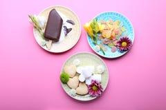 Diversos dulces sabrosos con las flores en el fondo rosado, visión superior Fotos de archivo