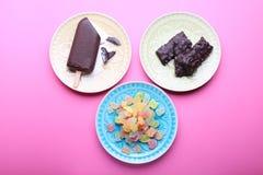 Diversos dulces sabrosos en las placas, fondo rosado Visión superior Foto de archivo libre de regalías