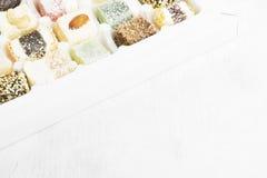 Diversos dulces turcos con las nueces, Cocos, sésamo en un blanco imagenes de archivo
