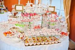 Diversos dulces y magdalenas en el tabl de la recepción nupcial del abastecimiento Foto de archivo libre de regalías