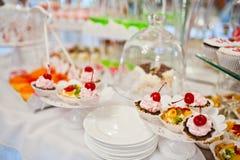 Diversos dulces y magdalenas en el tabl de la recepción nupcial del abastecimiento Imagen de archivo libre de regalías