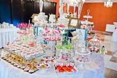 Diversos dulces y magdalenas en el tabl de la recepción nupcial del abastecimiento Imagen de archivo