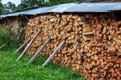 Diversos empilharam ordenadamente a lenha no pátio da vila Em suportes Imagens de Stock