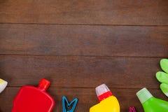 Diversos equipos de la limpieza dispuestos en piso de madera Imagen de archivo