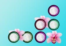 Diversos frascos do creme e das orquídeas de cara imagens de stock