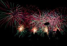 Diversos fuegos artificiales coloreados con la silueta de la gente Imágenes de archivo libres de regalías
