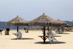 Diversos guarda-chuvas da cabana da tenda ajustaram-se sobre tabelas e cadeiras na praia Imagem de Stock Royalty Free