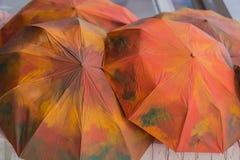 Diversos guarda-chuvas pintados em cores vermelho-alaranjadas do outono Fundo da queda estações Imagens de Stock